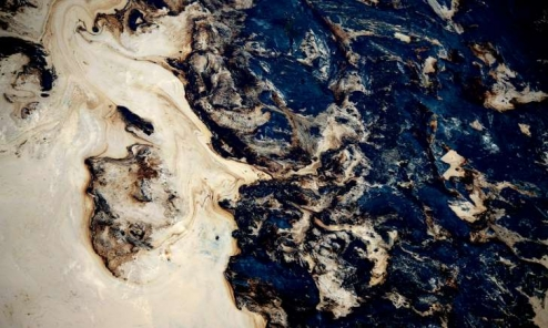 Toxic waste in a tailing pond at the Syncrude open pit oil excavation mine in Fort McMurray,Alberta, Canada, on 21 Jul 2009. The top soil is removed to give access to the controversial tar sands. The sand goes through a processing plant to extract usable oil.: A Guardian campaign backed by 95,000 people so far is asking the gates to sell their fossil fuel investments.